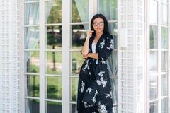 Ελκυστική νέα γυναίκα στα ενδύματα μεταξιού και τα μοντέρνα γυαλιά που θέτουν ενάντια στους stained-glass τοίχους ενός ακριβού στοκ εικόνα με δικαίωμα ελεύθερης χρήσης