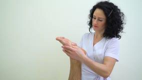 Ελκυστική νέα γυναίκα στο ομοιόμορφο να τρίψει πόδι ανδρών στο σαλόνι SPA απόθεμα βίντεο