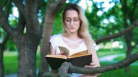 Ελκυστική νέα γυναίκα eyeglasses που διαβάζει ένα βιβλίο που κλίνει σε έναν κλάδο δέντρων απόθεμα βίντεο