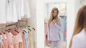 Ελκυστική νέα επιχειρηματίας που προσπαθεί στο φόρεμα και που κοιτάζει στον καθρέφτη για να δει πώς κοιτάζει σε το Προσπάθεια κορ απόθεμα βίντεο