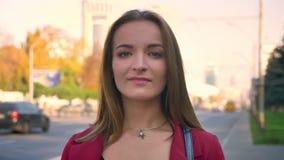 Ελκυστική νέα θηλυκή κινηματογράφηση σε πρώτο πλάνο που φαίνεται ευθεία στη κάμερα και το χαμόγελο, που στέκονται στο πεζοδρόμιο, απόθεμα βίντεο