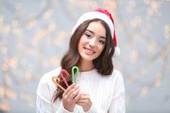 Ελκυστική νέα κυρία στους καλάμους καραμελών εκμετάλλευσης καπέλων Χριστουγέννων Στοκ Εικόνες