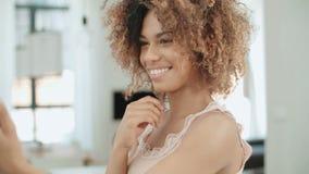 Ελκυστική νέα μαύρη γυναίκα που κάνει selfie στην κουζίνα απόθεμα βίντεο