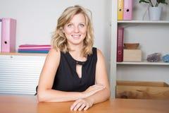 ελκυστική νέα ξανθή επιχειρηματίας με το καλό χαμόγελο στο γραφείο στοκ φωτογραφίες