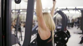 Ελκυστική νέα ξανθή καυκάσια γυναίκα με τη φίλαθλη κατάρτιση σωμάτων σκληρά σε ένα pull-down lat mashine στη γυμναστική Υγιής απόθεμα βίντεο