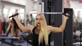 Ελκυστική νέα ξανθή καυκάσια γυναίκα με το φίλαθλο σώμα που εκτελεί σε ένα pull-down lat mashine στη γυμναστική απόθεμα βίντεο