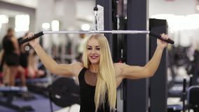Ελκυστική νέα ξανθή καυκάσια γυναίκα με το φίλαθλο χαμόγελο σωμάτων ασκώντας σε ένα pull-down lat mashine στη γυμναστική φιλμ μικρού μήκους
