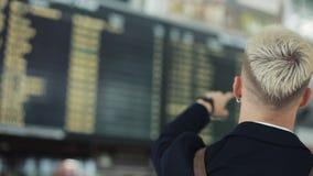 Ελκυστική νέα περιμένοντας τροφή επιχειρηματιών στο σαλόνι αναχώρησης στον αερολιμένα Αυτός που εξετάζει το έξυπνο ρολόι φιλμ μικρού μήκους