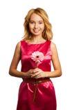 Ελκυστική ξανθή γυναίκα που κρατά ένα λουλούδι στοκ εικόνες