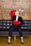 Ελκυστική ξανθή επιχειρηματίας με τα εγκιβωτίζοντας γάντια έτοιμα για μια πάλη μπροστά από ένα διαμέρισμα χρυσή ιδιοκτησία βασικώ Στοκ Εικόνες