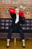 Ελκυστική ξανθή επιχειρηματίας με τα εγκιβωτίζοντας γάντια έτοιμα για μια πάλη μπροστά από ένα διαμέρισμα χρυσή ιδιοκτησία βασικώ Στοκ εικόνες με δικαίωμα ελεύθερης χρήσης