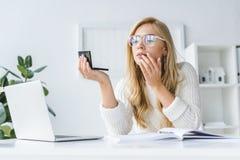 ελκυστική ξανθή επιχειρηματίας που κάνει makeup στον εργασιακό χώρο στοκ εικόνες