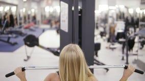 Ελκυστική ξανθή καυκάσια γυναίκα με το μυϊκό σώμα και δερματοστιξία σε την πίσω άσκηση σε ένα pull-down lat mashine απόθεμα βίντεο