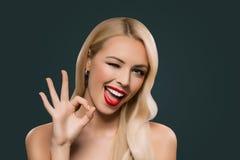 ελκυστική ξανθή κλείνοντας το μάτι γυναίκα που παρουσιάζει σημάδι okey, στοκ φωτογραφία με δικαίωμα ελεύθερης χρήσης