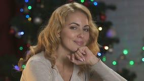 Ελκυστική ονειροπόλος γυναικεία συνεδρίαση στο υπόβαθρο του φωτισμένου χριστουγεννιάτικου δέντρου, χαρά απόθεμα βίντεο
