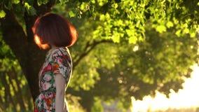 Ελκυστική περιστροφή κοριτσιών γύρω στο φως ηλιοβασιλέματος στο πάρκο r απόθεμα βίντεο