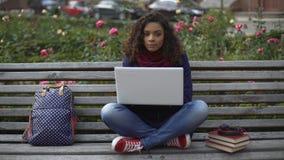 Ελκυστική σγουρός-μαλλιαρή γυναικεία συνεδρίαση στον πάγκο, που σκέφτεται για το πρόγραμμα εργασίας της απόθεμα βίντεο