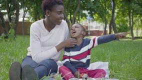 Ελκυστική συνεδρίαση γυναικών αφροαμερικάνων στο κάλυμμα με την λίγος γιος που παίζει με ένα παιχνίδι στο πάρκο Οι νεολαίες απόθεμα βίντεο
