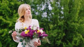 Ελκυστική τοποθέτηση νέων κοριτσιών στο δάσος με μια ανθοδέσμη των wildflowers άνοιξη απόθεμα βίντεο
