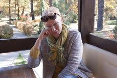 Ελκυστική ώριμη γυναίκα σε έναν πίνακα εστιατορίων σε μια ανοικτή βεράντα στοκ φωτογραφία με δικαίωμα ελεύθερης χρήσης