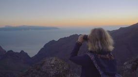 Ελκυστική ώριμη γυναίκα στην περιπέτεια πεζοπορίας σε μια κορυφή βουνών που εξετάζει τον ορίζοντα μέσω των διοπτρών φιλμ μικρού μήκους