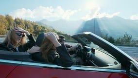 Ελκυστικοί ευρωπαϊκοί θηλυκοί φίλοι που τραγουδούν, που χορεύουν και που χτυπούν το οδηγώντας ανοικτό τοπ αυτοκίνητο πολυτέλειας  απόθεμα βίντεο