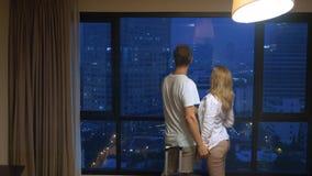 Ελκυστικοί ζεύγος, γυναίκα και άνδρας με μια βαλίτσα στο υπόβαθρο των ουρανοξυστών σε ένα πανοραμικό παράθυρο στο βράδυ στοκ εικόνες