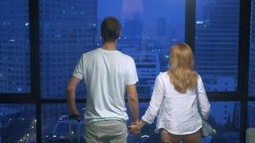 Ελκυστικοί ζεύγος, γυναίκα και άνδρας με μια βαλίτσα στο υπόβαθρο των ουρανοξυστών σε ένα πανοραμικό παράθυρο στο βράδυ στοκ φωτογραφία