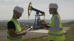 Ελκυστικοί θηλυκοί μηχανικός και επιστάτης που συζητούν για το πρόγραμμα εργασιών κοντά σε μια αντλώντας μονάδα πετρελαίου - φιλμ μικρού μήκους