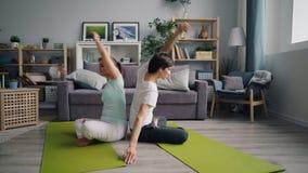 Ελκυστικοί τύπος και κορίτσι που κάνουν τις ασκήσεις γιόγκας ζευγαριού στην επίπεδη συνεδρίαση στο πάτωμα απόθεμα βίντεο