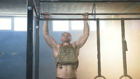Ελκυστικός αθλητής που κάνει το τράβηγμα UPS στη γυμναστική φιλμ μικρού μήκους