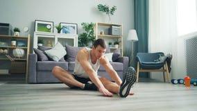 Ελκυστικός αθλητικός τύπος τύπων που κάνει τις τεντώνοντας ασκήσεις που κάμπτουν προς τα εμπρός σε ένα πόδι απόθεμα βίντεο