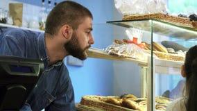 Ελκυστικός αρσενικός αρτοποιός που μιλά σε ένα μικρό κορίτσι στο κατάστημα αρτοποιείων του απόθεμα βίντεο