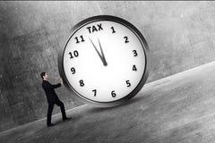 Ελκυστικός ασιατικός επιχειρηματίας που ωθεί ένα ρολόι με τη φορολογική προθεσμία Στοκ Εικόνα