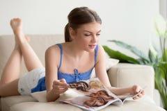Ελκυστικός αυτό περιοδικό ανάγνωσης κοριτσιών που βρίσκεται στον καναπέ στο σπίτι Στοκ Εικόνα