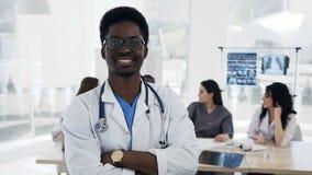 Ελκυστικός αφρικανικός αρσενικός γιατρός που κοιτάζει στη κάμερα με την ομάδα του cowoker στο υπόβαθρο στο νοσοκομείο απόθεμα βίντεο