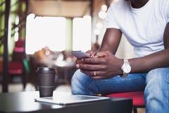 Ελκυστικός αφρικανικός επιχειρηματίας που χρησιμοποιεί το smartphone Έννοια των νέων που απασχολούνται στις κινητές συσκευές Κινη Στοκ Φωτογραφία
