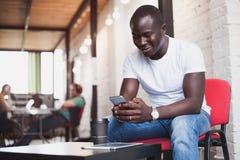 Ελκυστικός αφρικανικός επιχειρηματίας που χρησιμοποιεί το smartphone Έννοια των νέων που απασχολούνται στις κινητές συσκευές Κινη Στοκ Εικόνα