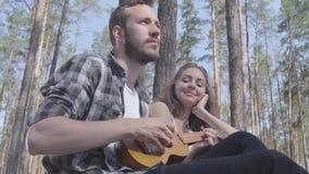 Ελκυστικός γενειοφόρος νεαρός άνδρας πορτρέτου που παίζει ukulele ενώ αρκετά νέα ευτυχής συνεδρίαση γυναικών πλησίον Αγαπώντας ζε απόθεμα βίντεο