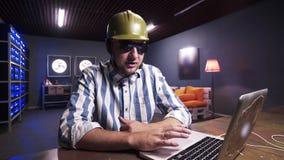 Ελκυστικός γενειοφόρος τύπος που τίθεται στα γυαλιά ηλίου και το πράσινο κράνος κατασκευής ασφάλειας απόθεμα βίντεο