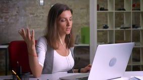 Ελκυστικός εργαζόμενος γραφείων θηλυκών στα ακουστικά που έχουν μια συνομιλία στο lap-top της στον εργασιακό χώρο στο εσωτερικό φιλμ μικρού μήκους