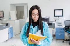 Ελκυστικός εργαζόμενος εργαστηρίων θηλυκών που κάνει τη ιατρική έρευνα στο σύγχρονο εργαστήριο Φάκελλος εγγράφων εκμετάλλευσης επ Στοκ Εικόνα