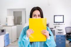 Ελκυστικός εργαζόμενος εργαστηρίων θηλυκών που κάνει τη ιατρική έρευνα στο σύγχρονο εργαστήριο Φάκελλος εγγράφων εκμετάλλευσης επ Στοκ φωτογραφία με δικαίωμα ελεύθερης χρήσης