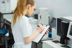 Ελκυστικός εργαζόμενος εργαστηρίων θηλυκών που κάνει τη ιατρική έρευνα στο σύγχρονο εργαστήριο Φάκελλος εγγράφων εκμετάλλευσης επ Στοκ εικόνες με δικαίωμα ελεύθερης χρήσης