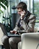Ελκυστικός ευρωπαϊκός τύπος που μιλά στο τηλέφωνο χρησιμοποιώντας το lap-top Στοκ εικόνες με δικαίωμα ελεύθερης χρήσης