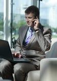 Ελκυστικός ευρωπαϊκός τύπος που μιλά στο τηλέφωνο χρησιμοποιώντας το lap-top Στοκ εικόνα με δικαίωμα ελεύθερης χρήσης
