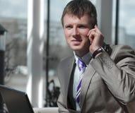 Ελκυστικός ευρωπαϊκός τύπος που μιλά στο τηλέφωνο χρησιμοποιώντας το lap-top Στοκ φωτογραφίες με δικαίωμα ελεύθερης χρήσης