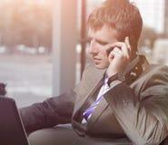 Ελκυστικός ευρωπαϊκός τύπος που μιλά στο τηλέφωνο χρησιμοποιώντας το lap-top Στοκ Φωτογραφίες