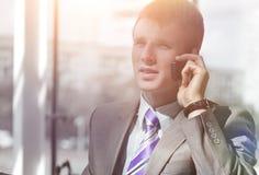 Ελκυστικός ευρωπαϊκός τύπος που μιλά στο τηλέφωνο χρησιμοποιώντας το lap-top Στοκ Φωτογραφία