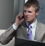 Ελκυστικός ευρωπαϊκός τύπος που μιλά στο τηλέφωνο χρησιμοποιώντας το lap-top Στοκ Εικόνες